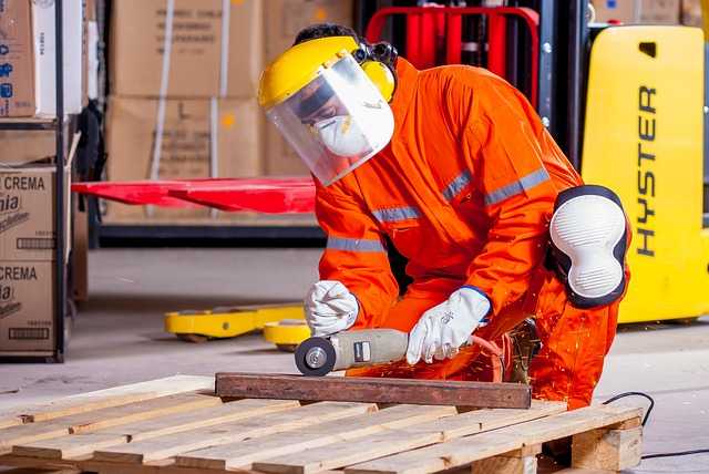 ochranné pomůcky při práci se dřevem – člověk, který upravuje paletu